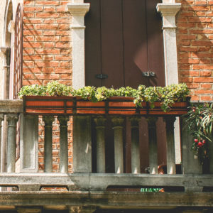 Brown planter boxes on a stone balcony.