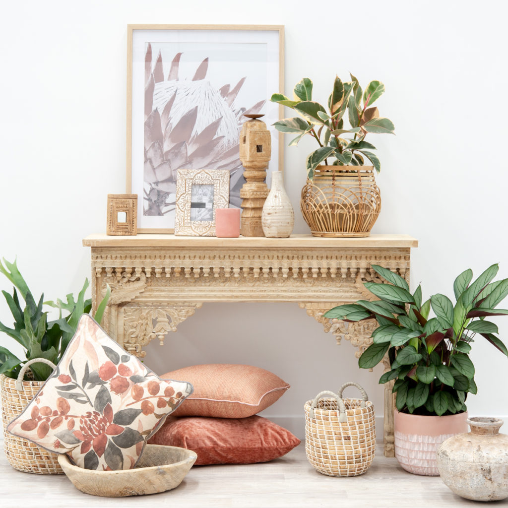 An ornately-carved sideboard laden with stunning homewares and plants in varying warm pink-based tones.
