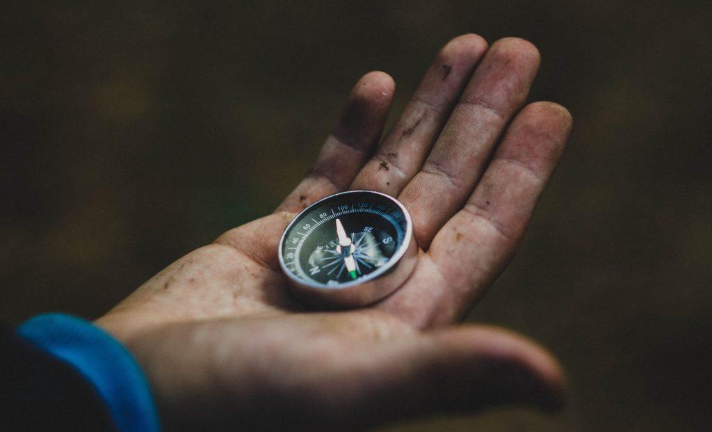 A dirt-clad hand holding a compass.